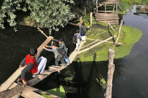 Kashmiri children cross a damaged footbridge built over a stream in India