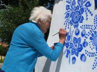 Grandmother Agnes Kašpárková delicately paints traditional Moravian ornament